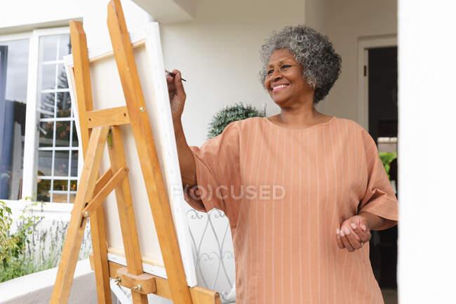 Mulher idosa afro-americana sorrindo enquanto pintava sobre tela em pé no alpendre da casa. permanecer em auto-isolamento em quarentena — Fotografia de Stock