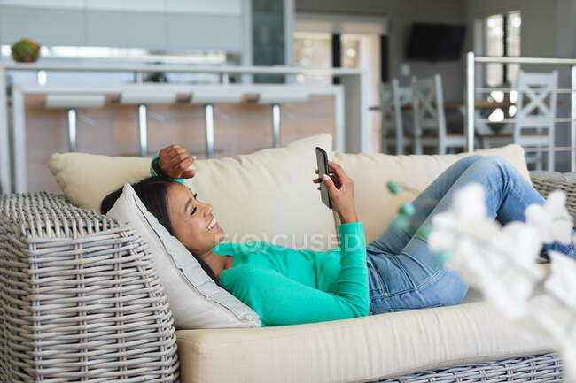 African american woman using smartphone lying on the couch at home. staying at home in self isolation in quarantine lockdown — Stock Photo