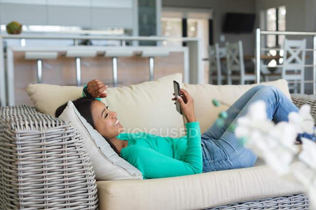 Afroamerikanerin mit Smartphone zu Hause auf der Couch liegend. Zu Hause bleiben in Selbstisolierung in Quarantäne — Stockfoto