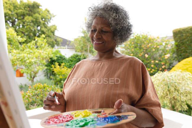 Eine afroamerikanische Seniorin lächelt, während sie auf der Veranda des Hauses auf Leinwand malt. Isolation in Quarantäne — Stockfoto