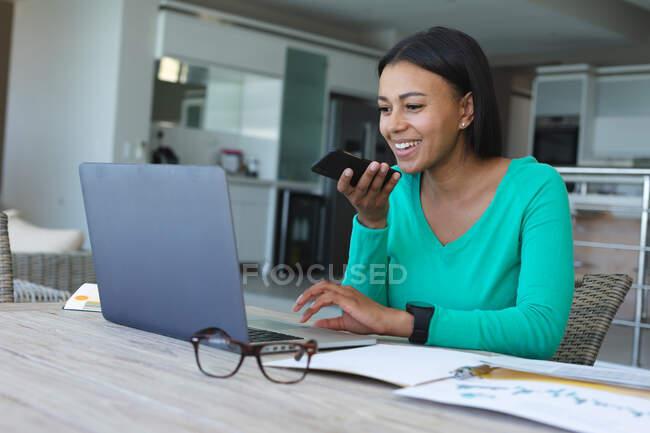 Africano americano mulher falando no smartphone e usando laptop enquanto trabalhava em casa. ficar em casa em auto-isolamento em quarentena — Fotografia de Stock