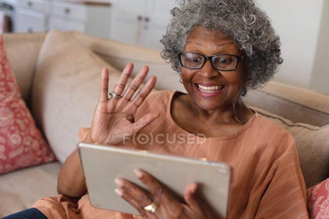 Femme âgée afro-américaine souriante et agitant tout en ayant un appel vidéo sur tablette numérique à la maison. rester à la maison en isolement personnel en quarantaine — Photo de stock