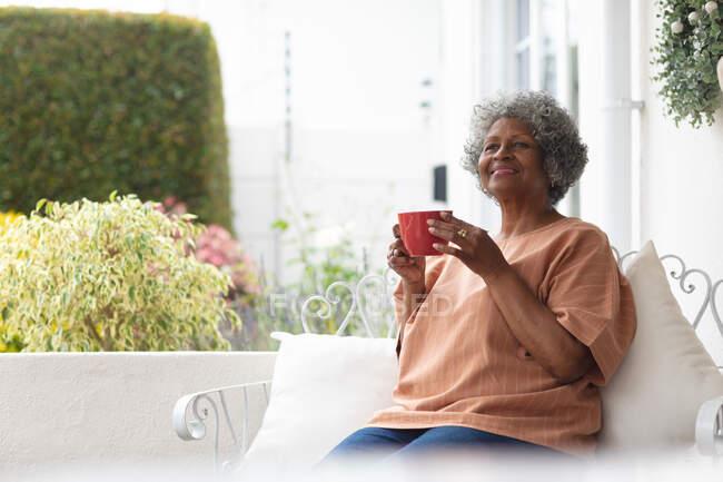 Mulher sênior afro-americana cuidadosa segurando xícara de café sorrindo enquanto estava sentada no alpendre da casa. permanecer em auto-isolamento em quarentena — Fotografia de Stock