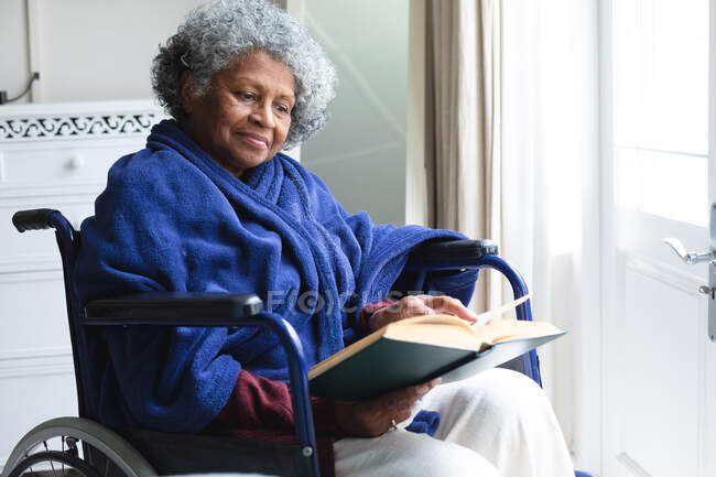 African american senior woman reading a book while sitting on wheelchair at home. staying at home in self isolation in quarantine lockdown — Stock Photo