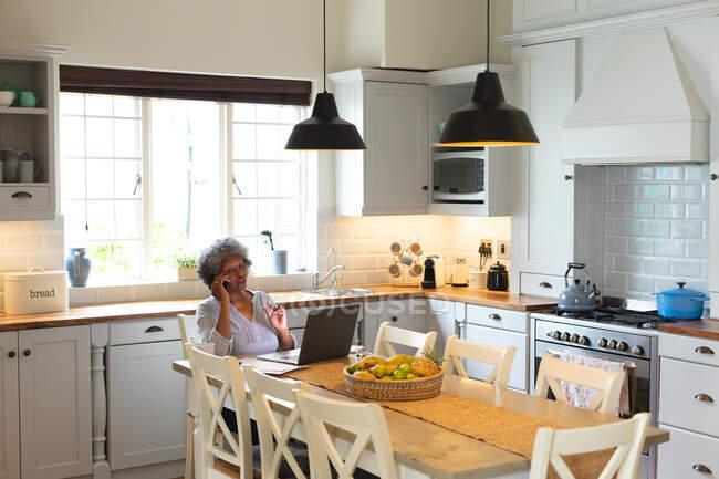 Африканська старша жінка-американка розмовляє на смартфоні вдома на кухні. Залишатися вдома в ізоляції в карантині. — стокове фото