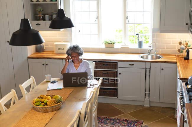 Африканская старшая женщина разговаривает на смартфоне и использует ноутбук на кухне дома. оставаться дома в изоляции в карантинной изоляции — стоковое фото