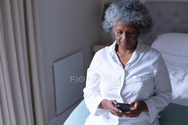 Nachdenkliche afrikanisch-amerikanische Seniorin mit Smartphone, während sie zu Hause im Bett sitzt. Zu Hause bleiben in Selbstisolierung in Quarantäne — Stockfoto