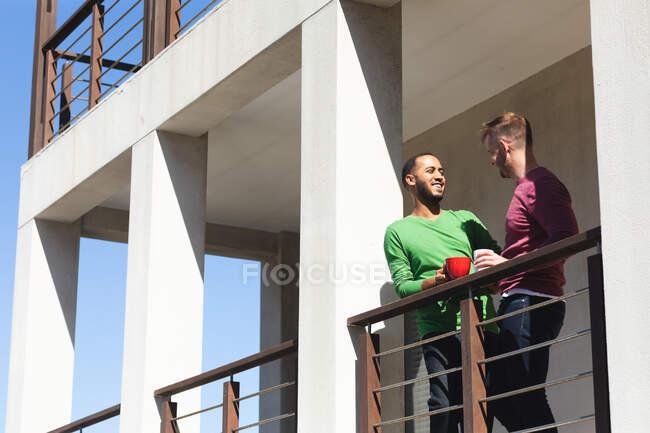 Multi-ethnische schwule männliche Paare lächeln und trinken Kaffee auf dem Balkon in der Sonne. Zu Hause bleiben in Selbstisolierung während Quarantäne Lockdown. — Stockfoto