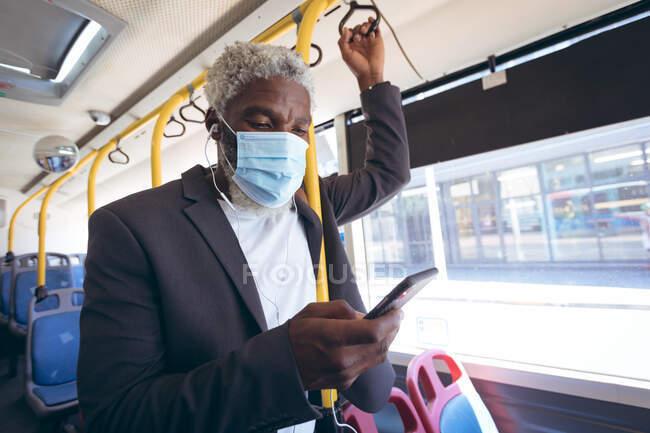 Afrikanischer älterer Mann mit Mundschutz und Kopfhörer, der mit dem Smartphone im Bus steht. digitaler Nomade unterwegs in der Stadt während Coronavirus covid 19 Pandemie. — Stockfoto