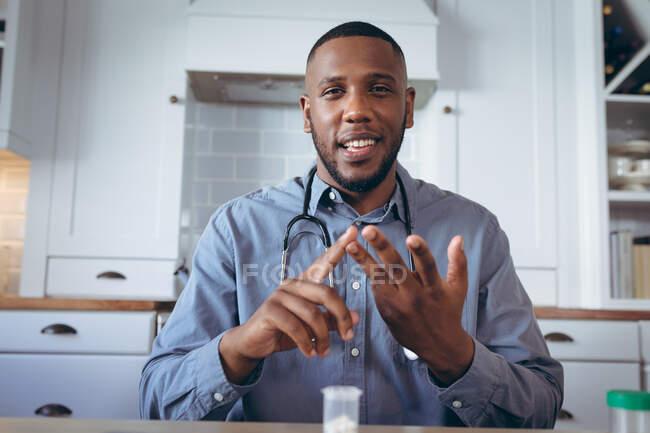 Médico afro-americano a ter uma conversa por vídeo. ficar em casa em auto-isolamento durante o confinamento de quarentena. — Fotografia de Stock
