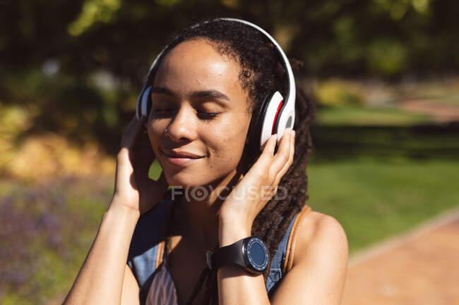 Улыбающаяся африканская американка в наушниках, стоящая на скутере и слушающая музыку на улице. Цифровой кочевник на ходу. — стоковое фото