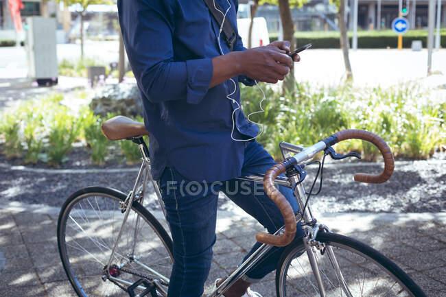 Низька частина чоловіка в навушниках сидить на велосипеді на вулиці за допомогою смартфона. Цифровий кочівник і все в місті. — стокове фото