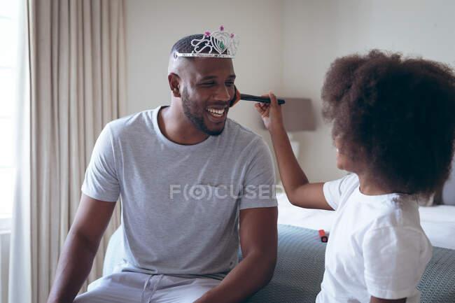 Afroamerikanischer Mann mit Diadem, geschminkt von seiner Tochter. Während der Quarantäne zu Hause bleiben und sich selbst isolieren. — Stockfoto