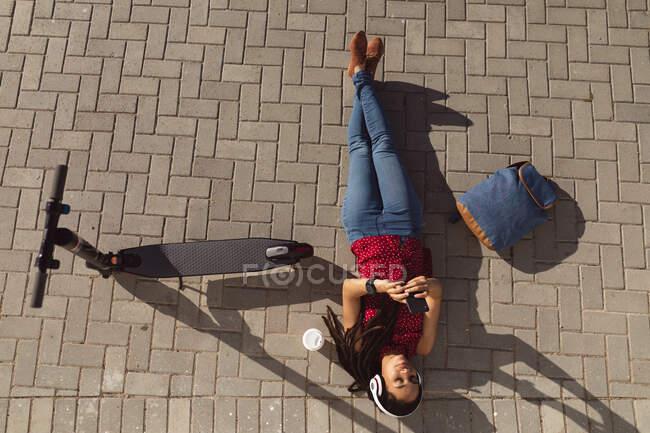 Mujer afroamericana relajante, acostada en el pavimento y usando un teléfono inteligente, scooter a su lado. Nómada digital sobre la marcha estilo de vida. - foto de stock