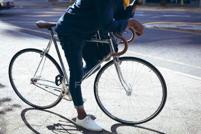 Низька ділянка старшого чоловіка, який спирається на велосипед на вулиці, розмовляє на смартфоні. Цифровий кочівник і близько в місті під час коронавірусу covid 19 пандемії. — стокове фото