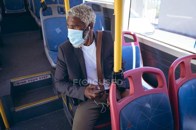 Африканський старший чоловік в масці обличчя і навушники сидять на автобусі з смартфоном. Цифровий кочівник і близько в місті під час коронавірусу covid 19 пандемії. — стокове фото