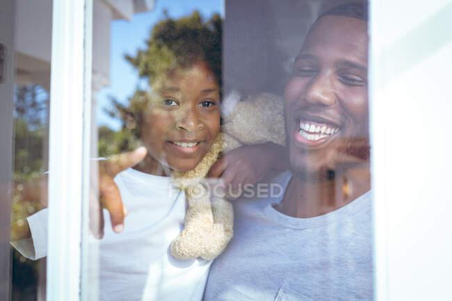 Afroamerikanerin und ihr Vater halten einen Teddybär in der Hand, der durch das Fenster schaut. Während der Quarantäne zu Hause bleiben und sich selbst isolieren. — Stockfoto