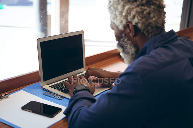 African american senior man sitting at table in cafe working using laptop. digital nomad out and about in the city. — Stock Photo