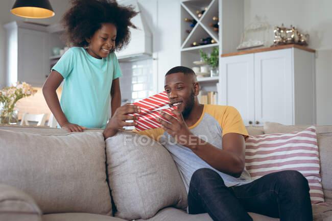 Chica afroamericana de pie en la sala de estar dando a su padre un regalo. permanecer en casa en aislamiento durante el bloqueo de cuarentena. - foto de stock
