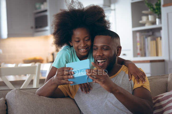 African american girl standing in living room giving her father a present. staying at home in self isolation during quarantine lockdown. — Stock Photo