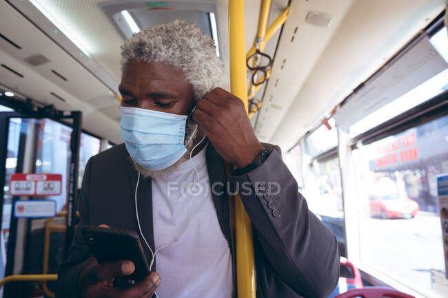 African american senior man wearing face mask putting on earphones standing on bus using smartphone. digital nomad out and about in the city during coronavirus covid 19 pandemic. — Stock Photo