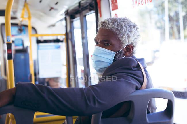 Ein älterer afroamerikanischer Mann mit Gesichtsmaske sitzt im Bus und dreht sich um, um auszusehen. digitaler Nomade unterwegs in der Stadt während Coronavirus covid 19 Pandemie. — Stockfoto