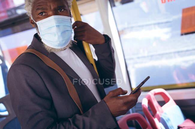 Африканський старший чоловік в масці на обличчі стоїть на автобусі за допомогою смартфона. Цифровий кочівник і близько в місті під час коронавірусу covid 19 пандемії. — стокове фото