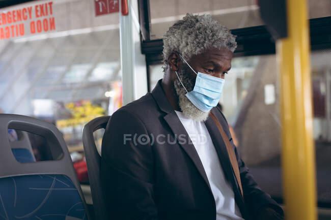 Ein älterer afroamerikanischer Mann mit Mundschutz sitzt im Bus. digitaler Nomade unterwegs in der Stadt während Coronavirus covid 19 Pandemie. — Stockfoto