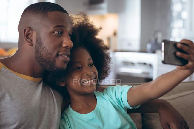 Африканська дівчинка-американка, яка сидить на дивані, робить селфі зі своїм батьком. Перебуваючи вдома в ізоляції під час карантину.. — стокове фото