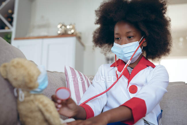 Chica afroamericana jugando al doctor y paciente con su osito de peluche. permanecer en casa en aislamiento durante el bloqueo de cuarentena. - foto de stock