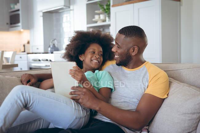 Африканська американка сидить на дивані, використовуючи цифрову табличку зі своїм батьком. Перебуваючи вдома в ізоляції під час карантину.. — стокове фото