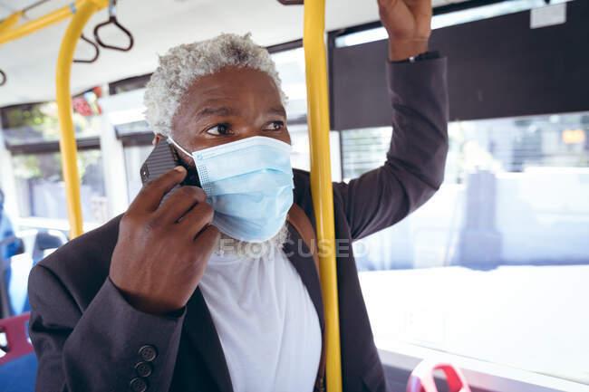 Afro-americano sênior vestindo máscara facial de pé no ônibus falando no smartphone. nômade digital para fora e sobre na cidade durante coronavírus covid 19 pandemia. — Fotografia de Stock