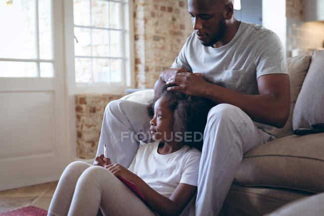 Afroamerikaner sitzt auf dem Bett und frisiert seine Tochter. Während der Quarantäne zu Hause bleiben und sich selbst isolieren. — Stockfoto