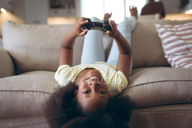 African american lying on a couch playing video games. staying at home in self isolation during quarantine lockdown. — Stock Photo