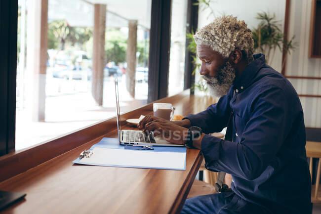 Afro-americano idoso sentado à mesa no café a trabalhar com laptop. nômade digital para fora e sobre na cidade. — Fotografia de Stock