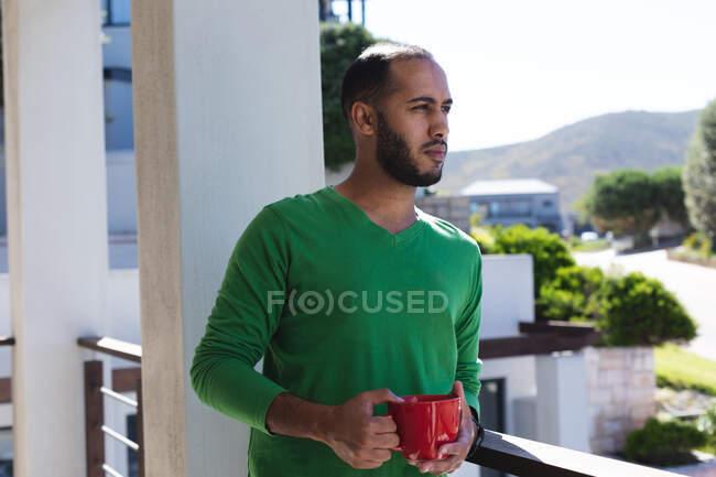 Homme métis réfléchi boire une tasse de café sur le balcon au soleil, vue admirative. Rester à la maison en isolement personnel pendant le confinement en quarantaine. — Photo de stock