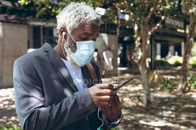 Африканський старший чоловік в масці і навушниках стоїть на вулиці за допомогою смартфона. Цифровий кочівник і близько в місті під час коронавірусу covid 19 пандемії. — стокове фото