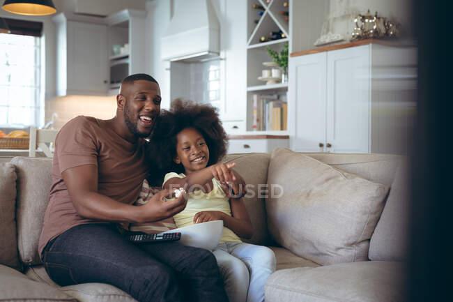 Африканский американец и его дочь сидят на диване и смотрят телевизор вместе. оставаться дома в изоляции во время карантинной изоляции. — стоковое фото