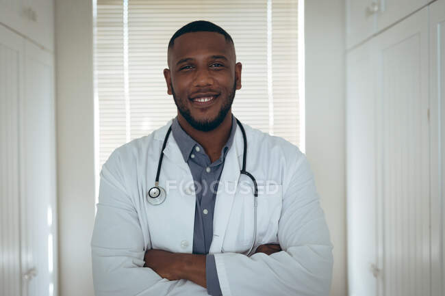 Portrait of african american male doctor looking at the camera and smiling. staying at home in self isolation during quarantine lockdown. — Stock Photo