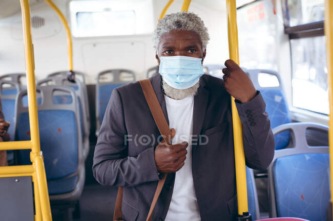 African american senior man wearing face mask standing on bus. digital nomad out and about in the city during coronavirus covid 19 pandemic. — Stock Photo