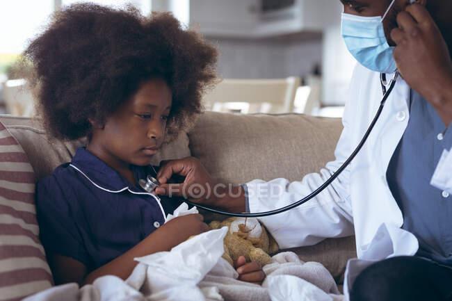 Medico afroamericano di sesso maschile che usa uno stetoscopio su un paziente infantile. stare a casa in isolamento durante l'isolamento in quarantena. — Foto stock