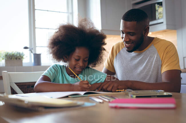 African american girl doing homework with her father. staying at home in self isolation during quarantine lockdown. — Stock Photo