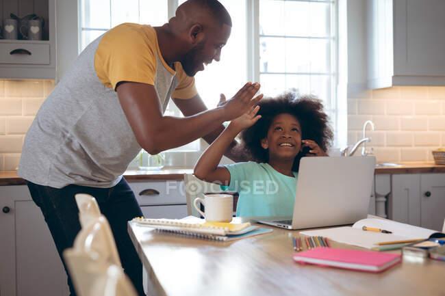 Afroamerikanerin mit Laptop und ihrem Vater. Während der Quarantäne zu Hause bleiben und sich selbst isolieren. — Stockfoto