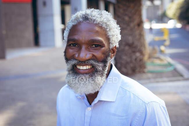 Porträt eines afrikanisch-amerikanischen älteren Mannes mit Bart, der auf der Straße lächelnd ein Hemd trägt. digitaler Nomade in der Stadt unterwegs. — Stockfoto