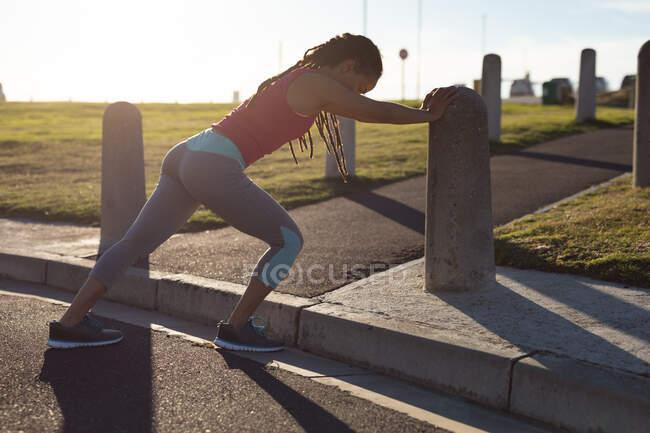 Африканская американка, занимающаяся спортом в парке, прислоняется к стене, растягивается. Здоровый образ жизни на открытом воздухе. — стоковое фото