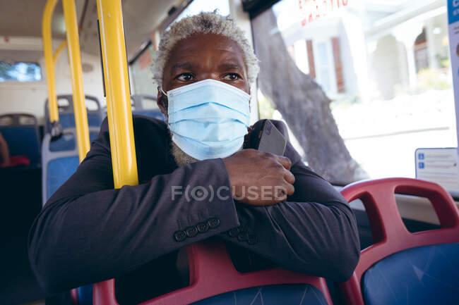 Африканський старший чоловік в масці на обличчі сидить на автобусі з смартфоном. Цифровий кочівник і близько в місті під час коронавірусу covid 19 пандемії. — стокове фото
