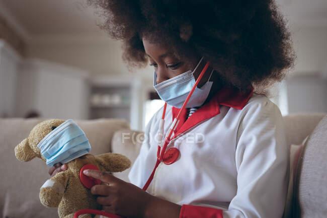 Menina afro-americana jogando médico e paciente com seu ursinho de pelúcia. ficar em casa em auto-isolamento durante o confinamento de quarentena. — Fotografia de Stock