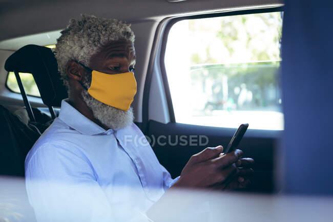 Homem sênior afro-americano usando máscara facial sentado em táxi táxi usando smartphone. nômade digital para fora e sobre na cidade durante coronavírus covid 19 pandemia. — Fotografia de Stock