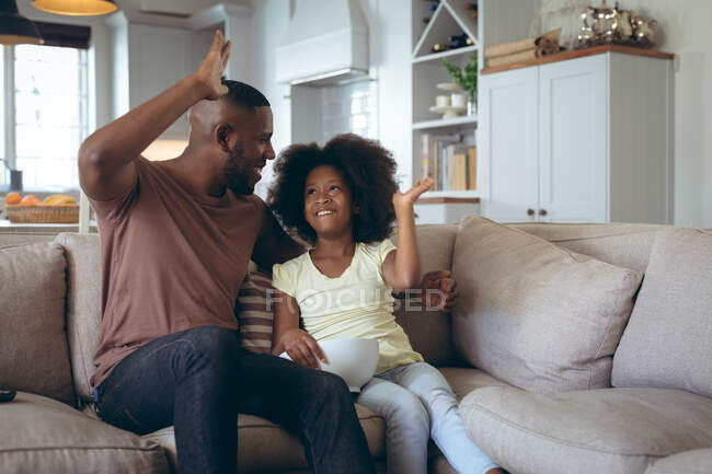 African american man and his daughter sitting on couch high fiving. staying at home in self isolation during quarantine lockdown. — Stock Photo