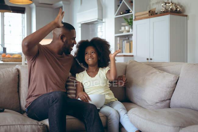 Африканский американец и его дочь сидят на диване, давая пять. оставаться дома в изоляции во время карантинной изоляции. — стоковое фото
